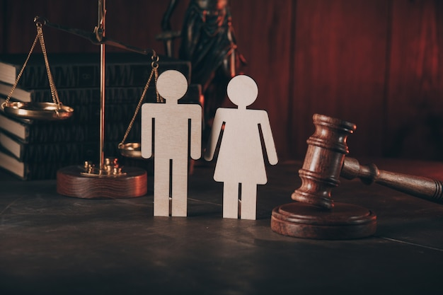 Figure in shape of people and gavel on wooden table.