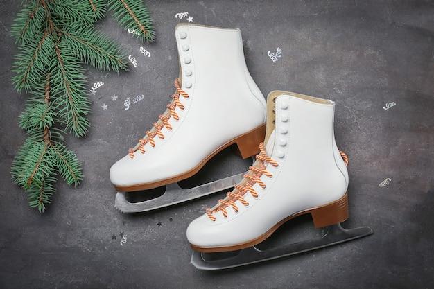灰色の背景にモミの枝を持つフィギュアスケート