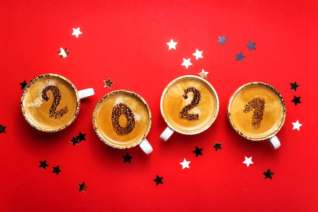 Figures 2021 as a symbol of the new year on cups of hot aromatic coffee on a bright red
