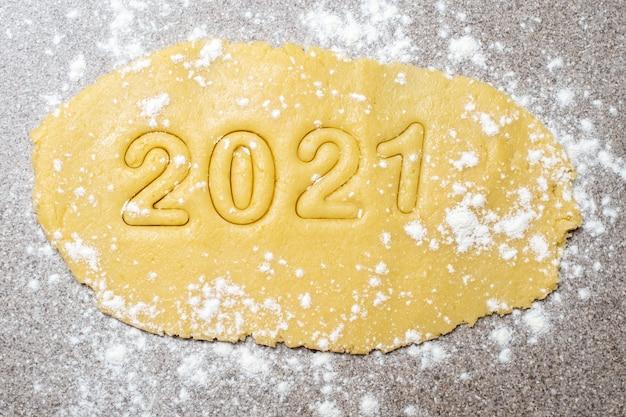 Фигурки 2021 года на желтом тесте, присыпанном мукой или сахарной пудрой. новогодняя вечеринка Premium Фотографии