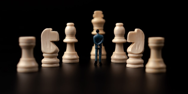 Figures businessman standing in front of wooden chess on black isolated background.