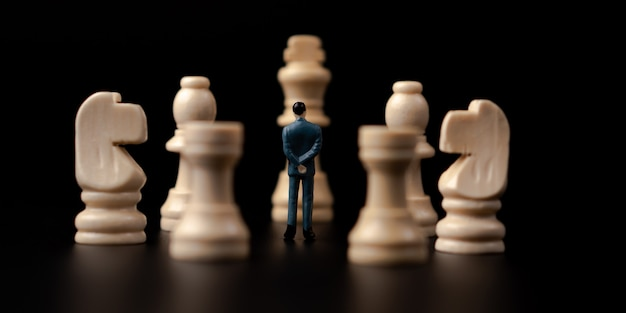 Figures businessman standing in front of wooden chess.