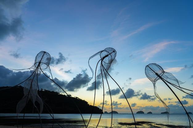 Figures of jellyfish on sunset sky.