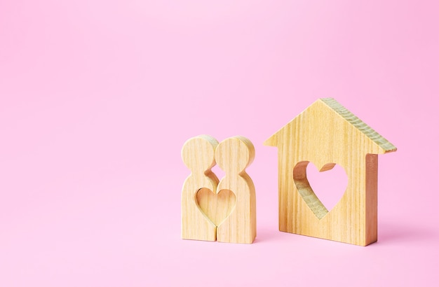 Figures of a love couple stand near house with a heart. affordable cheap housing for young couples