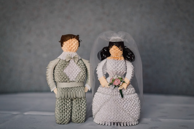 Figures of newlyweds made of grey paper