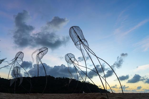 Фигуры медуз на фоне закатного неба.