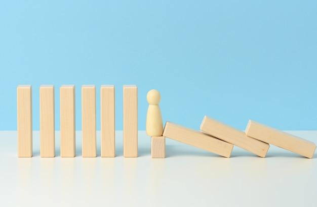 男性の姿は、ドミノの効果である木製のブロックの落下を抑制します。チームワークの概念