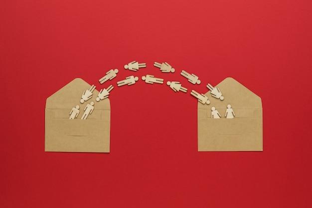 Фигуры людей, летающих между двумя открытыми конвертами на красном фоне.