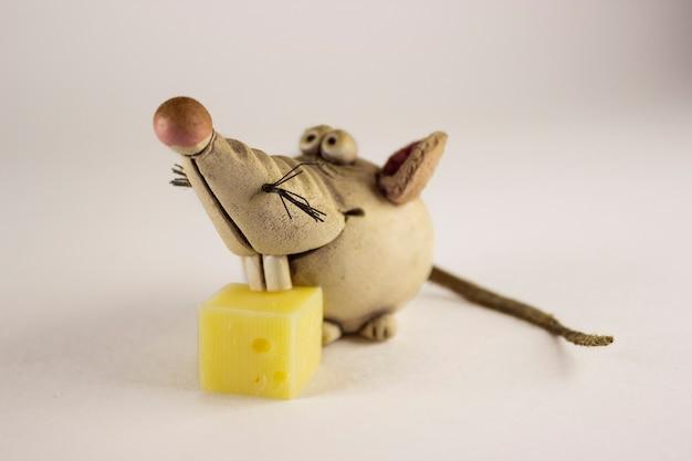ネズミの図と白い背景の上のチーズの一部。マウスの小像、クローズアップ。新年のコンセプト。セレクティブフォーカス。