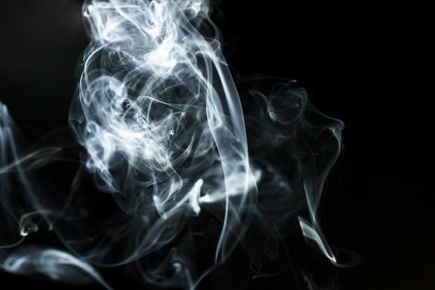 Фигуры белого дыма на черном фоне