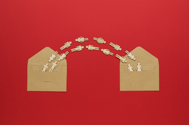 Figures of people flying between two open envelopes on a red background.