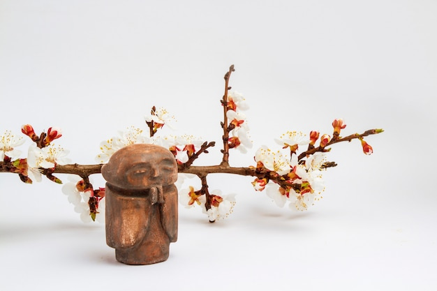 Figurine of a buddhist monk and a branch of a cherry tree with flowers . concept of spring and chinese new year.