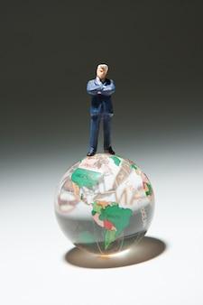 Figurine of businessmen standing on glass globe