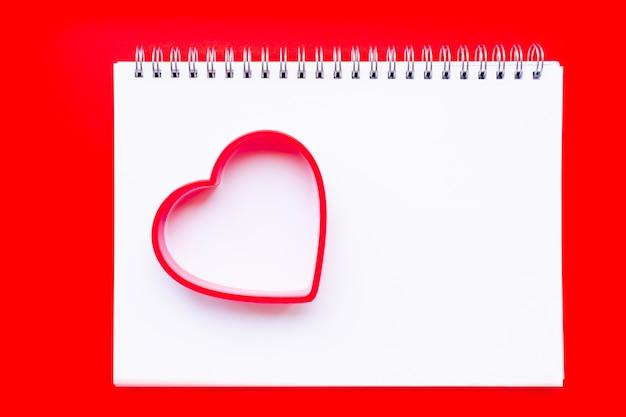 クッキーの置物のハートは、らせん状のノートブックの開いたページにあります。無地の赤い背景。バレンタインデーのコンセプト