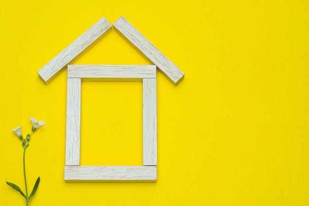 Фигурка домика из деревянных блоков на желтом
