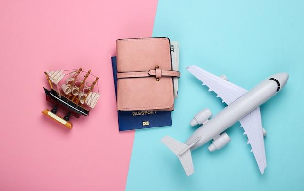 Фигурка корабля, самолета, паспорта и камердинера на сине-розовой пастели.