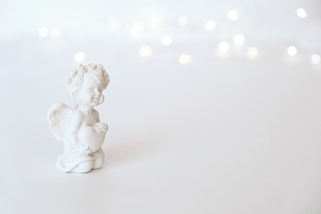 ピンクの背景に弓を持つ天使のキューピッドの置物。バレンタイン・デー。