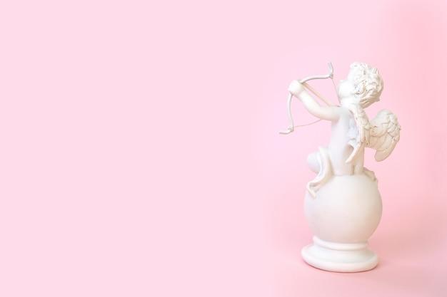 ピンクの壁に弓を持った天使のキューピッドの置物。バレンタイン・デー。