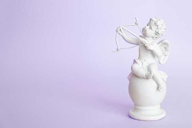 紫色の背景に弓を持つ天使のキューピッドの置物。バレンタイン・デー。