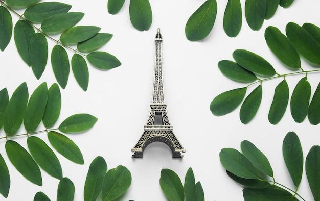 Фигурка эйфелевой башни на белом фоне с зелеными листьями.