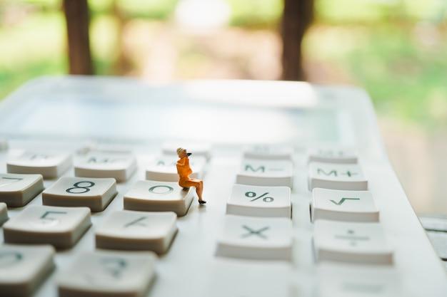 Figurine person sitting on calculator