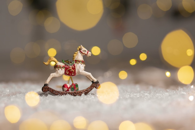 Figurine of a rocking horse festive decor, warm bokeh lights.