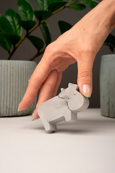 Figurine toy animal handmade concrete and plaster cow in woman hand for playing with children and