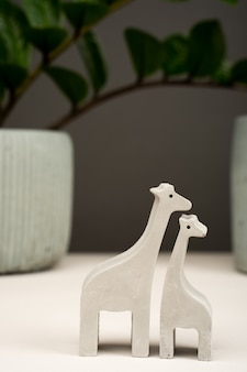 Figurine toy animal handmade concrete and plaster mom and baby giraffe for playing with children and minimalistic decor and home decoration.