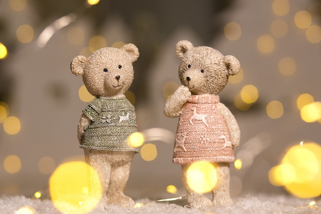 Figurines of cute teddy bears of a boy and a girl in sweaters with deers