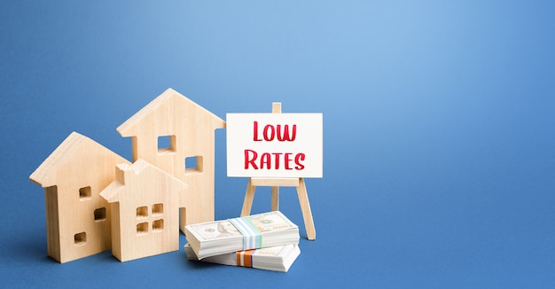 Figurines of houses and an easel with low rates. low demand for real estate and housing