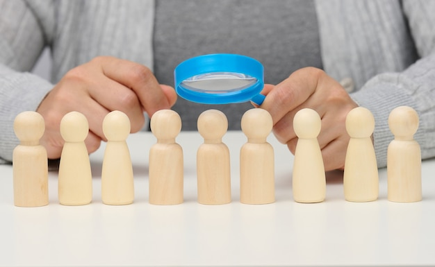 Figurines of men on a white table, a female hand holds a magnifying glass over one. concept of searching for employees in the company, recruiting personnel, identifying talented and strong personaliti