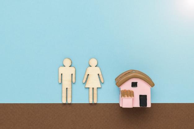 茶色と青の背景に家の置物の近くにある男性と女性の置物。