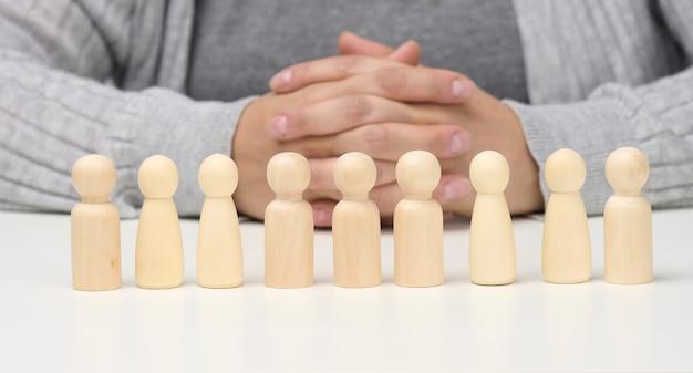Фигурки мужчин на белом столе. концепция поиска сотрудников в компании, подбор персонала, выявление талантливых и сильных личностей