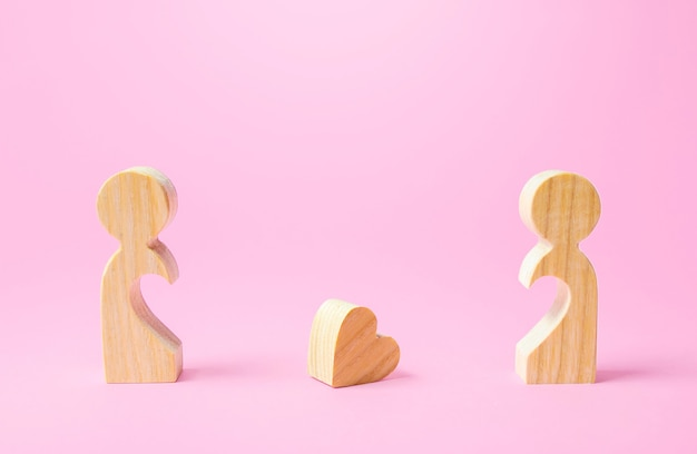 Figurines of people separated from each other and a lost heart. breakup, end of love