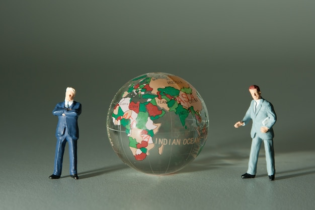 Figurines of two businessmen and glass globe