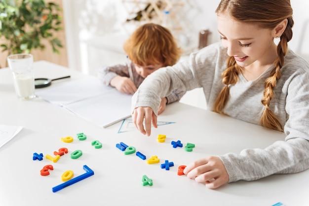결과 파악. 특별한 게임을 사용하여 그에게 몇 가지 유용한 트릭을 설명하는 그녀의 동생과 함께 숙제를하고 귀여운 부지런 예쁜 소녀 프리미엄 사진