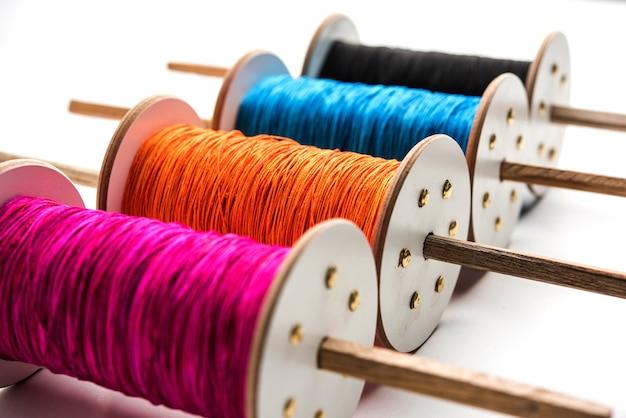 Fikri or reel은 chakri or spool로도 알려져 있으며 다채로운 실 또는 manjha가 있는 연 날리기에 사용됩니다. 흰색 배경 위에 선택적 포커스