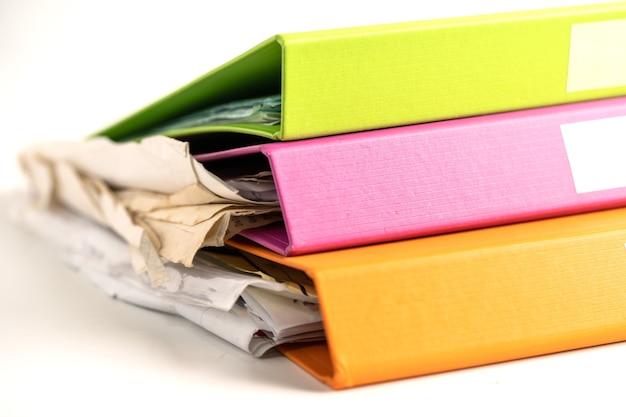 비즈니스 사무실의 테이블에 있는 여러 색상의 파일 폴더 바인더 스택입니다.