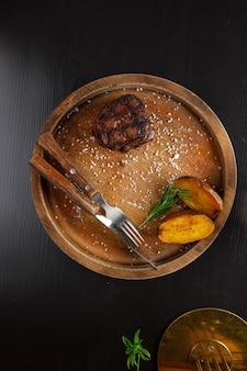 구운 감자와 함께 나무 접시에 제공되는 필레 미뇽 미디엄 레어