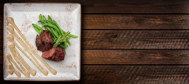 Филе миньон на белой квадратной тарелке со спаржей и соусом.