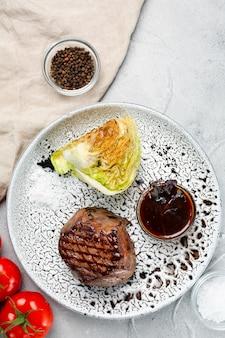 Филе миньон на крупном плане керамической плиты на конкретном столе. мясо с жареной капустой с соусом барбекю, вид сверху с ингредиентами