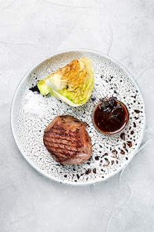 Филе миньон на крупном плане керамической плиты на конкретном столе. мясо с жареной капустой с соусом барбекю вид сверху