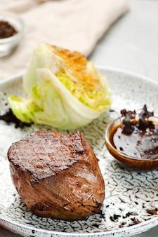 Филе миньон на крупном плане керамической плиты на конкретном столе. мясо с капустой гриль с соусом барбекю