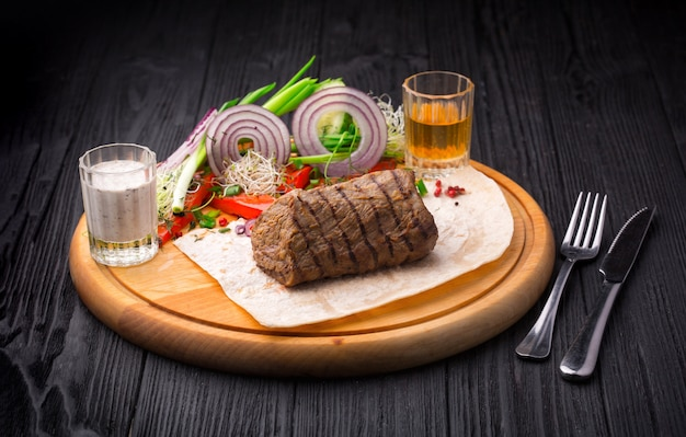 Filet mignon steak with garnish on wooden board