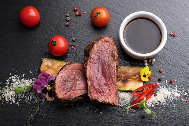 Filet mignon steak with sauce on black slate