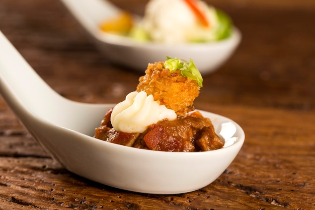 Filet mignon with spices, lemon zest, creamy curd and fried banana in a spoon. taste gastronomy fingerfood