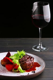 야채 샐러드와 레드 와인 한 잔을 곁들인 필레 미뇽. 테이블과 검정색 배경에 필레 미뇽이 있는 접시.
