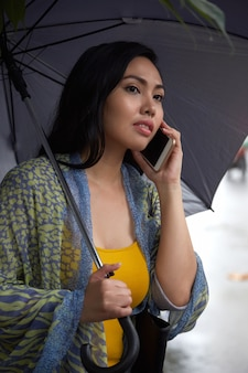 電話で話す傘を持つフィリピン人女性