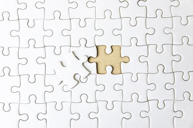 白いジグソーコンセプトパズルの欠けている部分の断片を埋めて成功する
