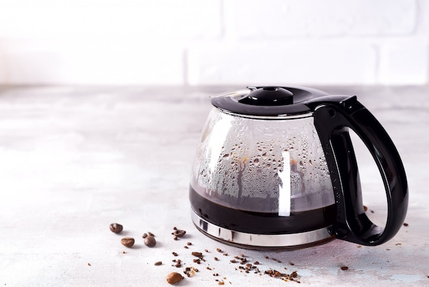 A filled coffee pot with coffee beans against a stone gray background